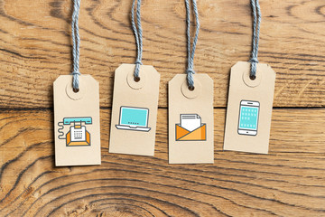Hangtags on wooden background with contact option icons