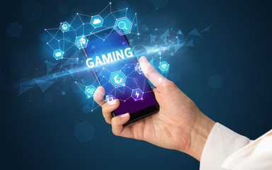 Female hand holding smartphone with GAMING inscription, modern technology concept