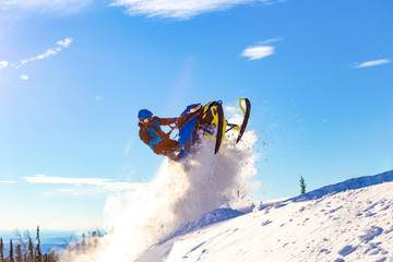 snowmobile jump. bright snowmobile in motion. the guy is flying on a snowmobile on a background of blue sky leaving a trail of splashes of white snow. bright snowmobile and suit without brands. super Wall mural