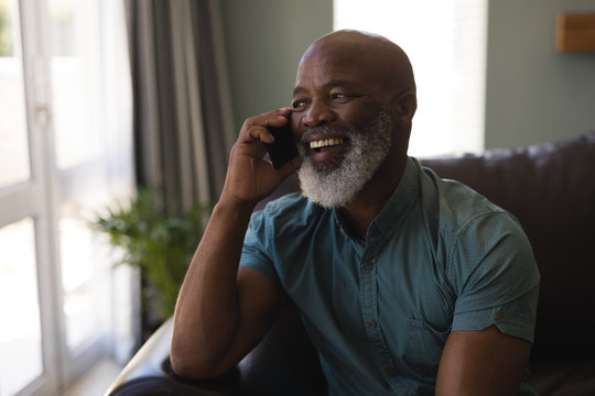 Senior man talking on mobile phone in living room