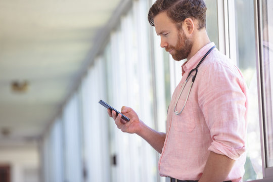 Male doctor using mobile phone while standing at nursing home corridor