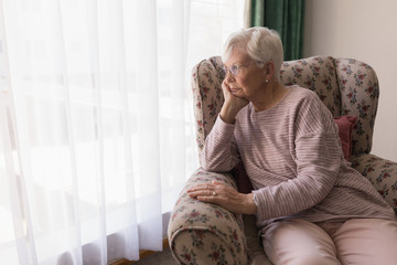 Front view of senior woman sitting on the couch and looking outside through window