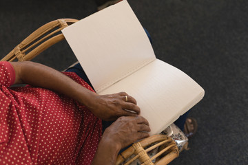 Blind senior man reading a braille book at nursing home