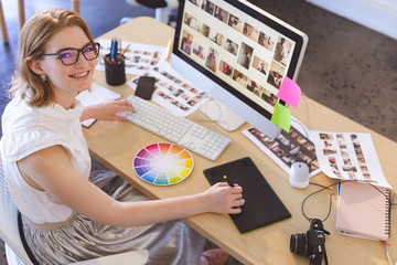 Female graphic designer working on graphic tablet at desk in office