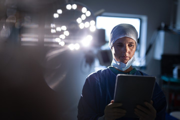 Female surgeon using digital tablet in operation room