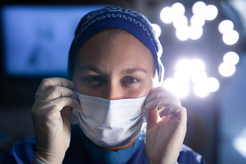 Female surgeon  putting on medical mask before operation