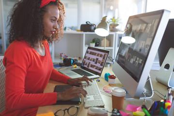 Female graphic designer working on desktop pc at desk