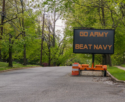 Electronic road sign on a suburban street that says Go Army Beat Navy