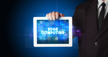 Young business person working on tablet and shows the inscription: EDGE COMPUTING