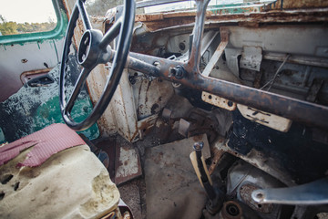 horizontal image of the inside of the front of a very old broken down bus