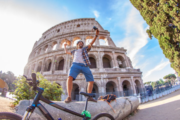 Happy young man tourist with bike wearing shirt and waving hat standing on a column taking selfies at colosseum in Rome, Italy at sunrise.