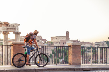 Young man tourist with backpack and bike cycling at Roman Forum at sunrise. Historical imperial...
