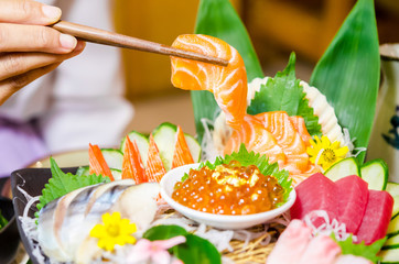 Salmon sashimi in chopsticks on sashimi set.