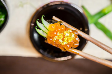 Wooden chopsticks tongs Gunkan Maki Sushi with salmon caviar (Ikura) and cucumber.
