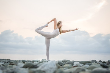 Elegant young beautiful athlete in tight-fitting costume is doing yoga virabhadrasana - stand on one leg standing on a rocky shore on a warm summer evening. Girl doing yoga, lifestyle healthy concept.