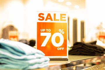 sale sign stands on a rack with things in the store