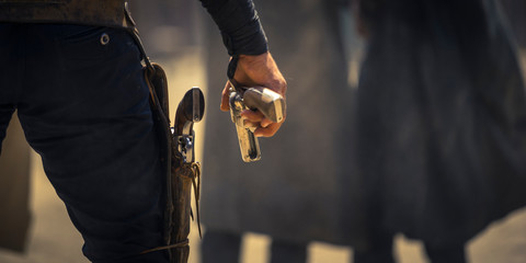 Man holding his six-shooter ready for a gunfight, Western movie set