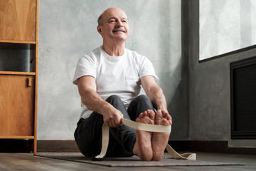 In de dag Ontspanning Senior hispanic man sitting in paschimottanasana or Intense Dorsal Stretch pose, seated forward bend posture, exercise for hips and spine at home using belt.