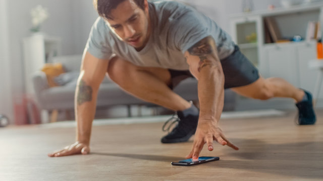 Muscular Athletic Fit Man in T-shirt and Shorts is Doing Mountain Climber Exercises While Using a Stopwatch on His Phone. He is Training at Home in His Bright Living Room with Minimalistic Interior.