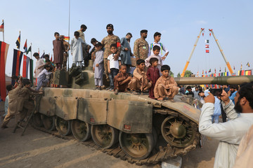 Men and children on a tank pose for pictures during Defence Day ceremonies, or Pakistan's Memorial Day, to express solidarity with the people of Kashmir, in Peshawar