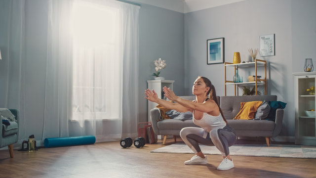 Strong and Beautiful Athletic Fitness Girl in Sportswear is Doing Squat Exercises in Her Bright and Spacious Living Room with Minimalistic Interior.