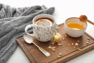Cup of hot tea with lemon, honey and flower on table