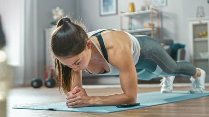 Obraz Strong Beautiful Fitness Girl in Athletic Workout Clothes is Doing a Plank Exercise While Using a Stopwatch on Her Phone. She is Training at Home in Her Living Room with Cozy Interior. - fototapety do salonu