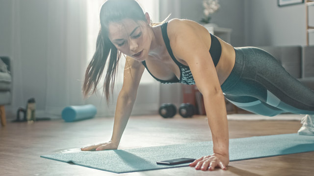 Close Up of a Beautiful Fitness Girl in an Athletic Top Doing Push Up Exercises While Looking at a Stopwatch on Her Phone. She is Training at Home in Her Living Room with Minimalistic Interior.