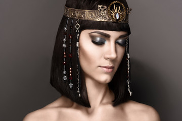 Glamorous closeup portrait of beautiful sexy stylish brunette young woman with bright makeup with perfect clean skin with gold jewelery. High fashion look. Beautiful Girl's Face Hairstyle Cleopatra