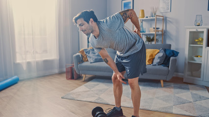 Muscular Athletic Shirtless Fit Man in Grey Shorts Injures His Back After Lifting Dumbbells at Home in His Spacious and Sunny Living Room with Minimalistic Interior.