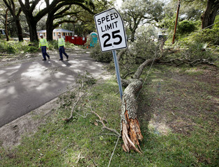 Utility workers walk past a power line brought down by a tree branch after Hurricane Dorian swept through, in Southport, North Carolina
