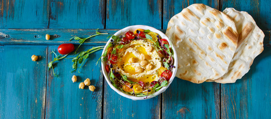 Hummus with olive oil, sprouts and tomatoes