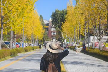 A woman is travel in the University in Korea during Autumn season. Fotobehang