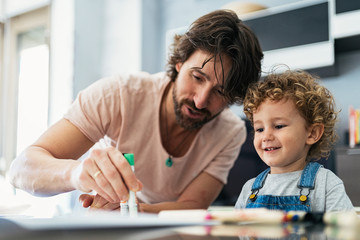 Adorable father and son drawing at home