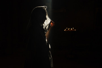 Mysterious lady standing in dark church
