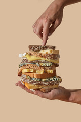 Male hands hold a healthy sandwich made from organic homemade bread with sesame and flax seeds and different cheese on a light brown background with space for text. Snack