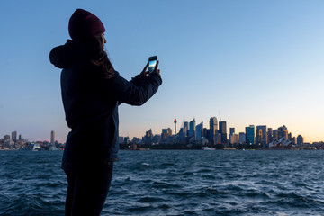 Woman photographing Sydney skyline at sunset