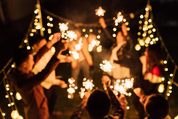 Group of friends holding burning sparklers and dancing