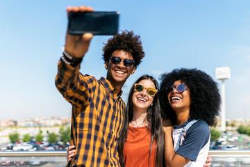 Group of happy friends taking a selfie in the street