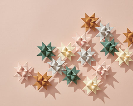 Holiday composition of different paper origami stars on a beige background with copy space. Layout for the new year or Christmas. Flat lay