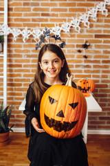 Girl holding Jack O Lantern pumpkin
