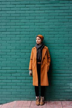 Stylish woman near green brick wall