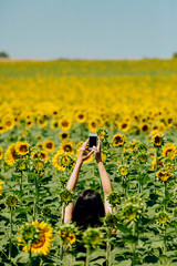woman taking pictures in a sunflowers field