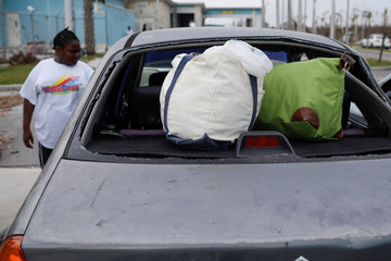 Bags are seen through a broken window of a car at the Leonard M. Thompson International Airport after Dorian hit the Abaco Islands in Marsh Harbour