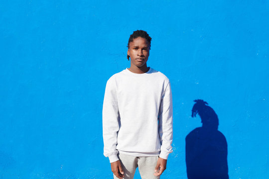 Modern black man in white on blue wall