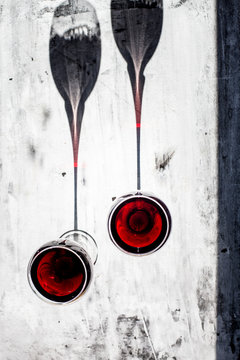 Overhead view of two glasses of red wine with shadows