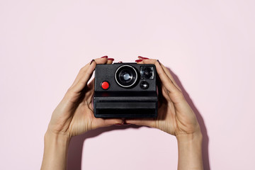 woman taking a photo with a polaroid camera