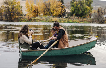 young mom takes pictures of family in rowboat