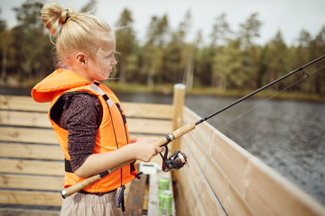 Cute little girl fishing off a dock during vacation