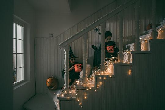 Children holding basket full with tretas from Halloween night